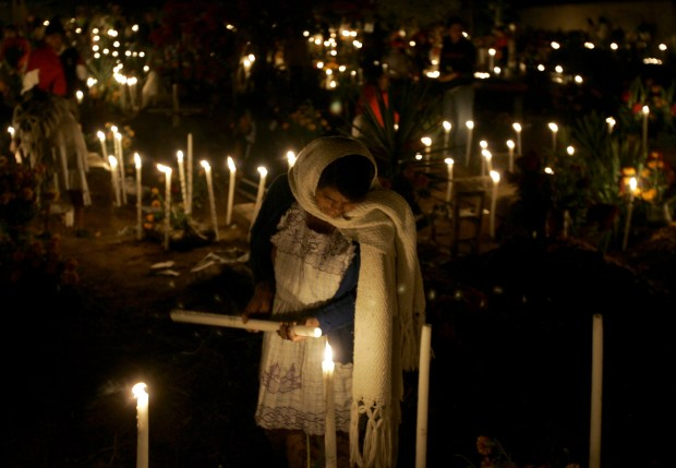 A woman visits the grave of relative with flowers and candles during of the Day of the Dead. (AP Photo/Eduardo Verdugo)