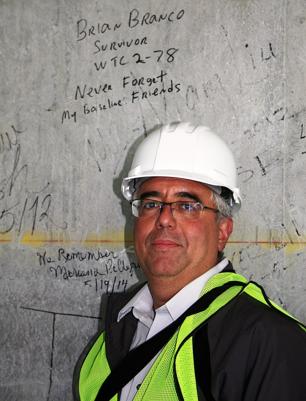 "Sept. 11, 2001, terrorist attack survivor Brian Branco of New Jersey stands on the 80th floor of 1 World Trade Center during construction on May 19, 2014. Branco signed the wall in memory of Thomson Financial/Baseline coworkers Steven Weinberg, Jill Maurer-Campbell and Robert ""Bob"" Levine, who died in the attack while Branco and one other coworker escaped the 78th floor of the World Trade Center's second tower. (Courtesy photo)"