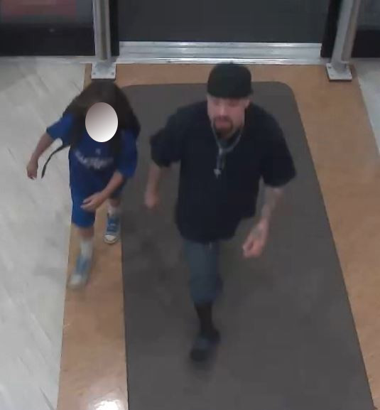 A man leaves a Glendale Rite-Aid on Oct . 26, 2017, after allegedly using this child to help steal liquor and candy. (Surveillance image provided by the Glendale Police Department)