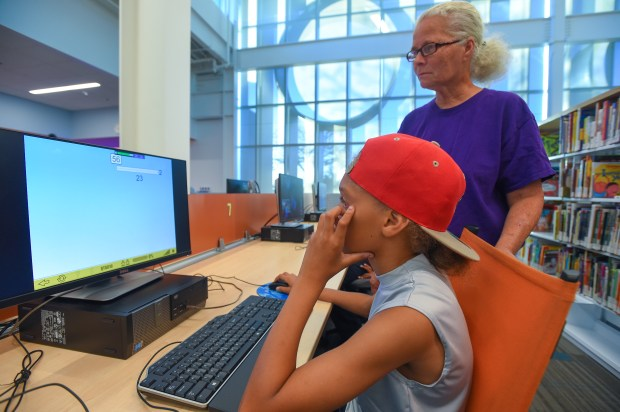 Vickie Jones looks over the shoulder of her grandson, Quincy Taylor, 10, as he works on his match homework on the computer at the Michelle Obama Library in North Long Beach on Thursday, November 9, 2017. Jones, who can't afford internet, spends each day after school with her grandsons as they do their homework on the computers at the library. (Photo by Scott Varley, Press-Telegram/SCNG)