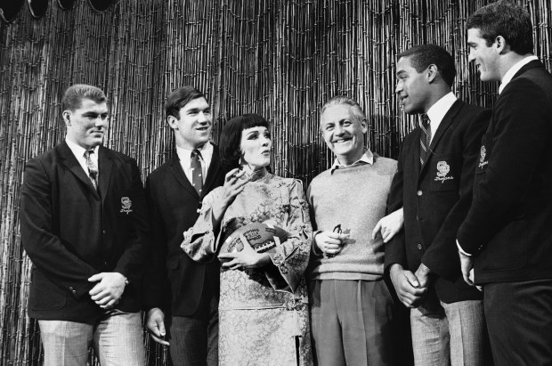 "Southern California football players, Ron Yary, Tim Rossovich, O.J. Simpson and Adrian Young, left to right, visit the set of the movie ""Star"" at 20th Century-Fox Studios in Hollywood, Dec. 13, 1967 and get a football autographed by movie star Julie Andrews. Also on hand is director Robert Wise, third from right, who directs the picture and who also directed Miss Andrews in the movie, ""The Sound of Music."" (AP Photo/David Smith)"