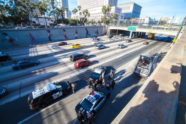 RefuseFascism.org provided this image of protesters being taken off the 101 Freeway Tuesday, Nov. 21, 2017, in downtown Los Angeles after they stopped traffic by unfurling an anti-Trump banner across the roadway. (Image courtesy of RefuseFacism LA)
