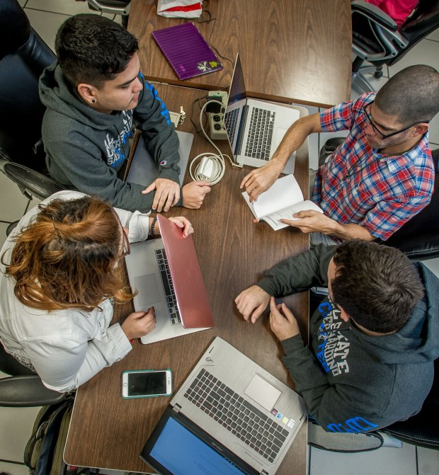 Graduate students, left to right, Naileen Berrios, Alexander Davila, Carlos Velez and Jadiel Colon work together at Cal State San Bernardino's Brown College of Business. Puerto Rican cybersecurity students, whose education was interrupted by Hurricane Irma, are continuing their education at CSUSB, Friday, Nov. 17, 2017. (Eric Reed/For The Sun/SCNG)