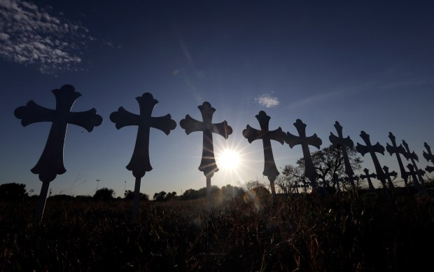 The sun sets behind 26 crosses placed in a field before a vigil for the victims of the First Baptist Church shooting Monday, Nov. 6, 2017, in Sutherland Springs, Texas. Texas officials confirmed Devin Patrick Kelley as the shooter who killed 26 people and wounded about 20 others at the church. (AP Photo/David J. Phillip)