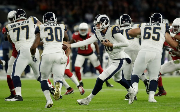 As Rams running back Todd Gurley (30) takes a hand off from Jared Goff, a hole opens thanks to Andrew Whitworth (77, left), Rodger Saffold and, far right,John Sullivan during the game against Arizona at Twickenham Stadium in London on Oct. 22. (AP Photo/Matt Dunham) Matt Dunham