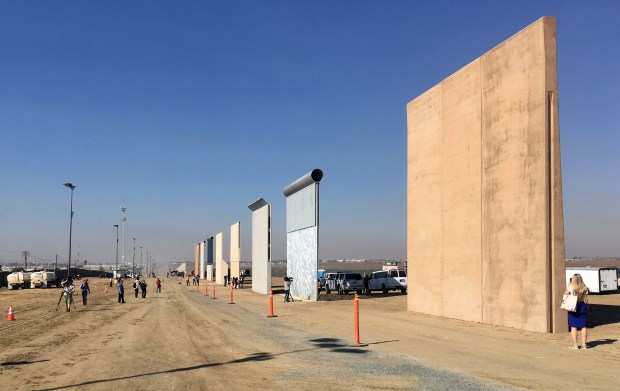 People look at prototypes of a border wall Thursday, Oct. 26, 2017, in San Diego. Contractors have completed eight prototypes of President Donald Trump's proposed border wall with Mexico, triggering a period of rigorous testing to determine if they can repel sledgehammers, torches, pickaxes and battery-operated tools. (AP Photo/Elliott Spagat)