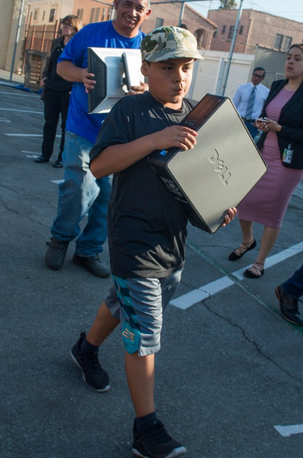 Kevin Vasquez, 9 of Los Angeles, walks away with a computer following an event in South Los Angeles on Thursday, August 3, 2017. The event was organized by Long Beach-based human-I-T, which refurbishes old computers and gives them to low-income families through a city of L.A. program. The partnership is an example of what could be done in Long Beach to help bridge the digital divide. (Photo by Thomas R. Cordova, Press-Telegram/SCNG)