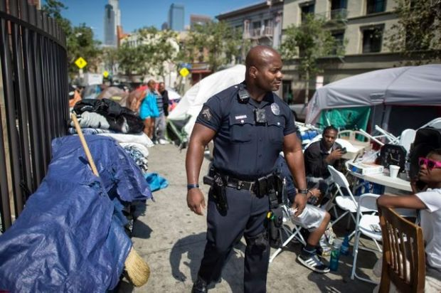 LAPD Officer Deon Joseph walks through the Skid Row area of Los Angeles, Wednesday, April 12, 2017. Officer Joseph has worked in Skid Row for almost two decades. (Photo by Hans Gutknecht, Los Angeles Daily News/SCNG)