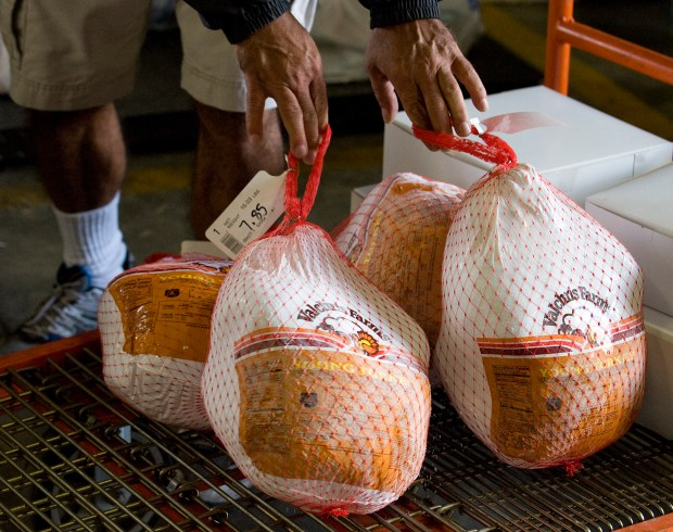 Residents take in donated turkeys at Tustin's Orange County Rescue Mission warehouse for a previous year's Thanksgiving meal. The nonprofit is looking for help to feed more than 660 people. (Photo by Jebb Harris, Orange County Register/SCNG)
