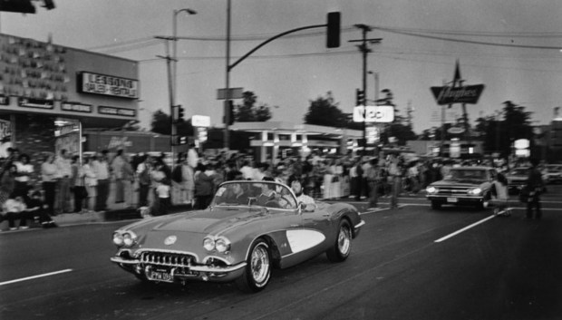 "In this May 15, 1986 photo, classic cruising-era Corvette motors along Van Nuys Boulevard before crowd of nostalgic onlookers during officially sanctioned revival banned in 1982."" (Photo courtesy Los Angeles Public Library)"