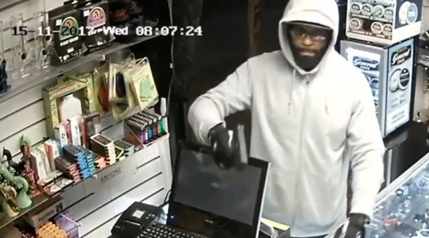 An armed man seen in this surveillance image robbed this store on the 5000 block of Wilshire Boulevard. He is described as black, about 30 to 40 years of age, around 6 feet tall and weighing about 200 pounds. (Image from surveillance video courtesy of the LAPD)