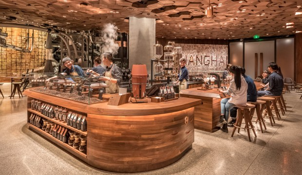 On Wednesday, Starbucks is opening its biggest cafe in the world in Shanghai. The 30,000 square-feet store — about half the size of a soccer field — is part of upscale moves championed by founder and Chairman Howard Schultz. Customers at the cavernous new outlet on the West Nanjing Road shopping strip can watch beans being roasted, sample high-end brews and use a Starbucks augmented-reality digital app to interact with the store. (Bloomberg)