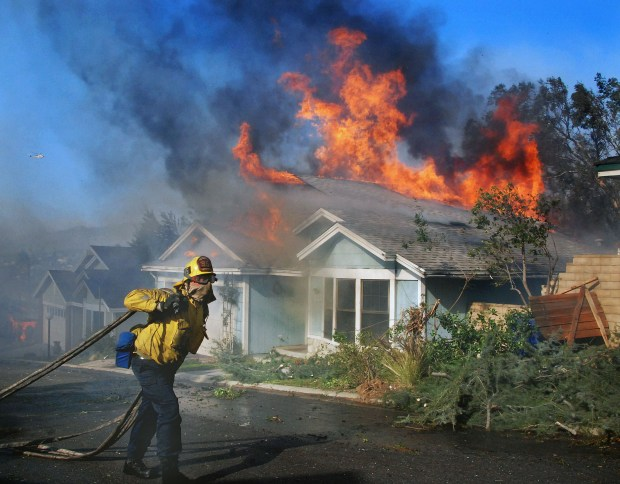 A LAFD firefighter fights to save a home in the Santiago Estates area of Sylmar this morning. The fight was unsuccessful as at least a half a dozen homes were lost when water pressure was lost on Tuesday, Dec.5, 2017. (Photo by Mike Meadows for the Los Angeles Daily News/SCNG)
