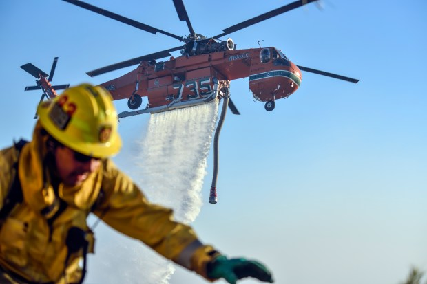 An LA City firefighters pulls hose around a house as a helicopter drops water during the Skirball Fire along Linda Flora Drive in the Bel Air neighborhood of Los Angeles, California, on Wednesday, December 6, 2017. (Photo by Jeff Gritchen, Orange County Register/SCNG)