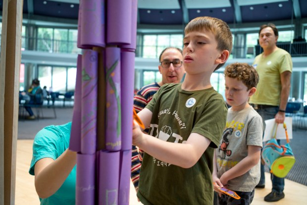 Jake Bernstein, 7, adds his artwork to a community menorah during the Hanukkah Festival at the Skirball Cultural Center Sunday, December 10, 2017. In background, dad, Craig Bernstein and friend Evan Whelan, 7, look on. The festival was moved indoors this year because of concerns over the air quality from recent fires. (Photo by David Crane/Los Angeles Daily News-SCNG)