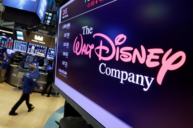 In this Aug. 8, 2017, file photo, The Walt Disney Co. logo appears on a screen above the floor of the New York Stock Exchange. Disney is buying a large part of the Murdoch family's 21st Century Fox in a $52.4 billion deal, announced Thursday, Dec. 14, 2017. (AP Photo/Richard Drew, File)