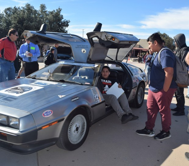 "Students at A.B. Miller High School in Fontana examine a 1981 DeLorean DMC-12 – a replica of the time machine from the movie ""Back to the Future"" – on display at the school's auto tech fair Dec. 11. (Courtesy photo)"