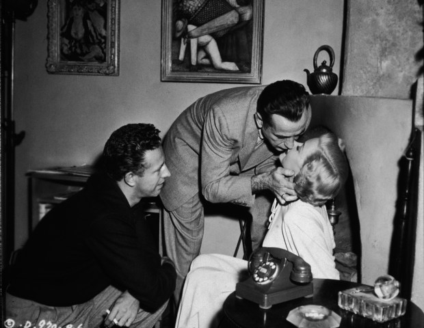 American film director Nicholas Ray (1911 - 1979) (left) directs American actor Humphrey Bogart (1899 - 1957) and Ray's second wife, American actress Gloria Grahame (1923 - 1981), as they rehearse a kiss on the set of the film 'In a Lonely Place,' Los Angeles, California, 1950. (Photo by Hulton Archive/Getty Images)