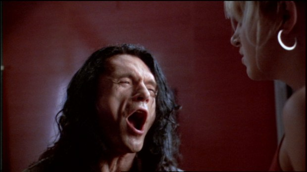"""Tommy Wiseau emotes in a scene from his film """"The Room"""" (courtesy of Fathom Entertainment)"""