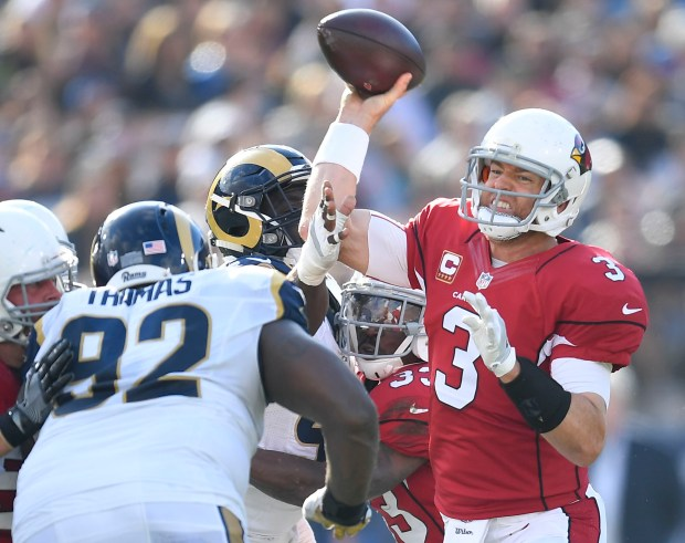 The Arizona Cardinals' Carson Palmer, now retired, throws under pressure from the Los Angeles Rams defense during the Rams' 44-6 loss to the Cardinals at the Los Angeles Memorial Coliseum in Los Angeles, Calif. on Sunday, January 1, 2017. (Photo by Kevin Sullivan, Orange County Register/SCNG)