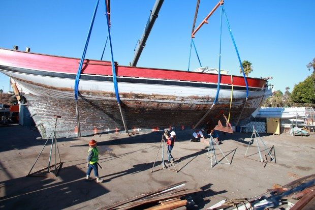 The Swift of Ipswich, built in 1938 and once serving as actor James Cagney's personal yacht, is being restored and will rejoin the Los Angeles Maritime Institute's fleet of tall ships used for youth sail training on San Pedro's waterfront. Workers hoist the 70-foot, wooden topsail schooner -- a replica of a Revolutionary War privateer -- onto a barge early Friday 1/5 morning to be brought back to San Pedro.  Photo By Michael Hare