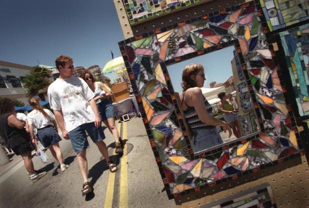 "Shoppers and tourists reflect on artwork while walking along Main St. observing the ""Art A-Faire"". A section of Main St. is regularly closed off to traffic Friday afternoons for this art event in Huntington Beach. (Photo by Lorren Au Jr.)"