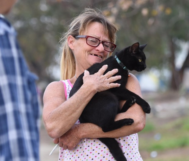 Lisa Weber holds a cat named Goodbye. She lives at the riverbed with her husband, Larry Ford. They moved near the Honda Center from the Fountain Valley tent encampment when it was dismantled in November. (Photo by Bill Alkofer, Orange County Register/SCNG)