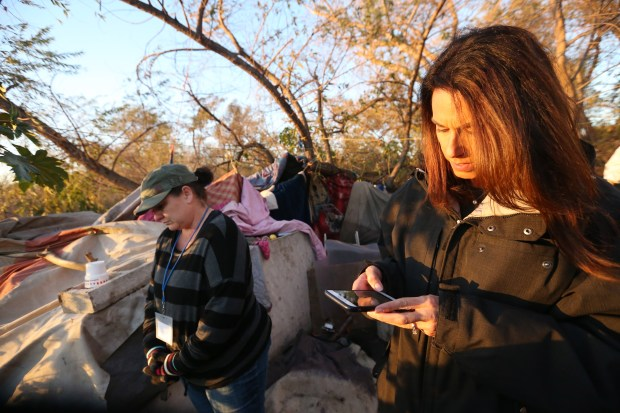 Former assistant director for the Riverside County Department of Public Social Services Lisa Shiner, fills out a survey on an app being tested as Stephanie Patton, a foster care eligibility technician for Department of Public Social Services, , interviews a homeless person living near a creek bed along Van Buren Blvd., during the annual Point-In-Time Homeless Count and survey in Jurupa Valley on Tuesday, Jan. 23, 2018. (Stan Lim, The Press-Enterprise/SCNG)