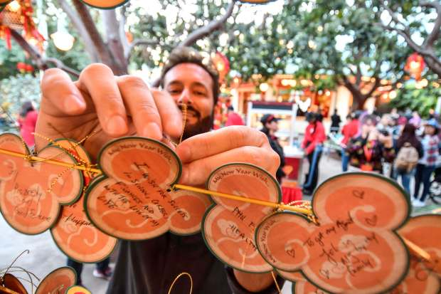 John Class hangs a new year wish on a line on the first day of Disney's Lunar New Year celebration at California Adventure in Anaheim on Friday, Jan 26, 2018. (Photo by Jeff Gritchen, Orange County Register/SCNG)