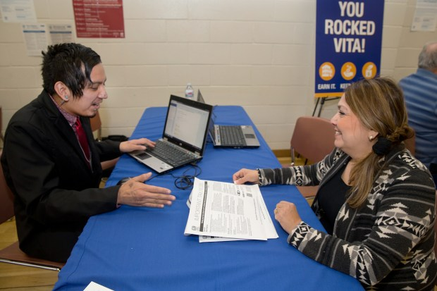 At an Anaheim free tax preparation fair, Eduardo Farfan, an IRS-trained volunteer, helps Yolanda Gentile, a customer service representative, with her return in January 2018. (Photo by David Kawashima/Orange County United Way)