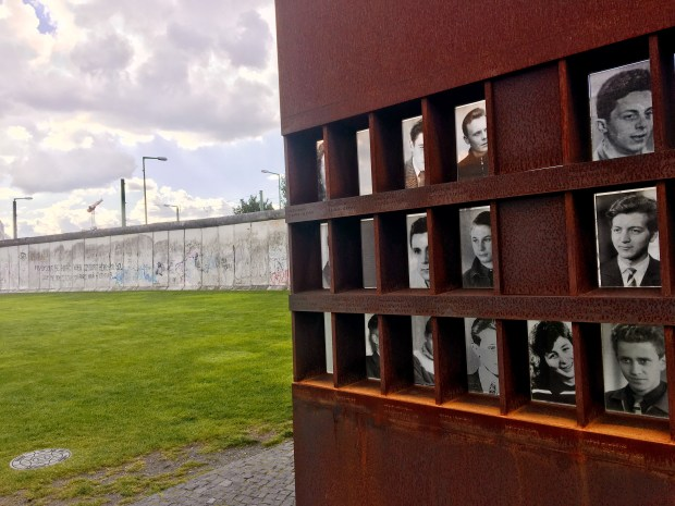 Memorial photos of victims who died at the Berlin Wall, along with an original piece of the wall that was left standing as an historical monument. Photo by Marla Jo Fisher, Sept. 2017.