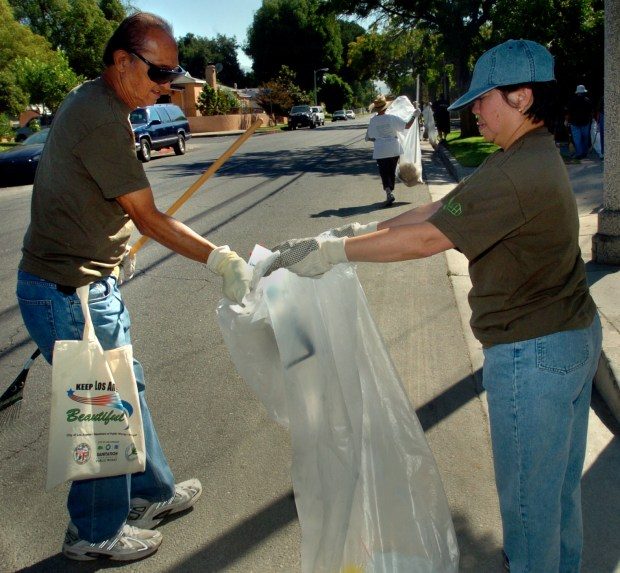 Johnny Borromeo of Panorama City places trash into a bag held by Connie Leoncio of Panorama City during the Panorama City Community Cleanup on September 15, 2007. (photo by Evan Yee, Los Angeles Daily News Staff Photographer)