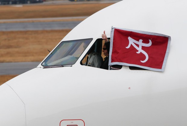 The pilot of the aircraft carrying the Alabama team home after winning the college football national championship game in Atlanta gives a thumbs up to fans at the Tuscaloosa Regional Airport in Tuscaloosa, Ala., on Tuesday morning. (Jake Arthur/The Tuscaloosa News via AP)