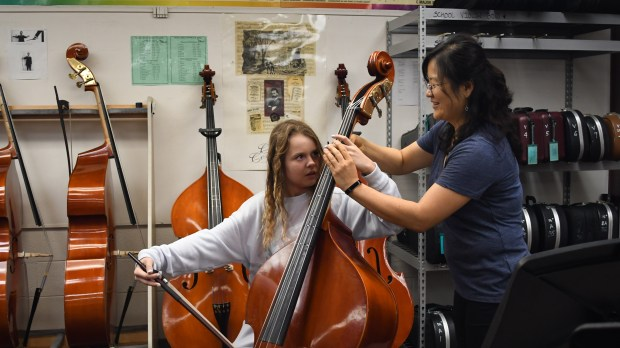 Orchestra Teacher Yeon Choi at Niguel Hills Middle School works with one of her students. (Photo courtesy of FundCru, Inc.)