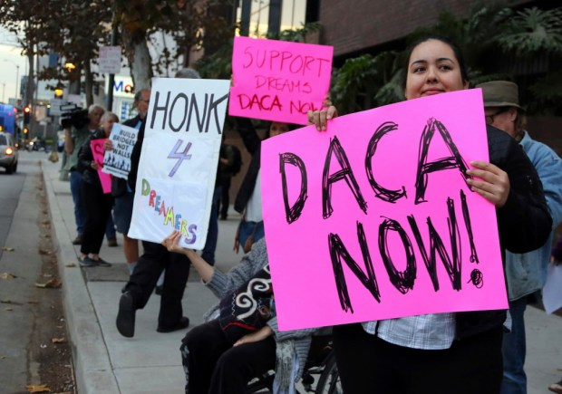 Demonstrators urging the Democratic Party to protect the Deferred Action for Childhood Arrivals Act (DACA) rally outside the office of California Democratic Sen. Dianne Feinstein in Los Angeles Wednesday, Jan. 3, 2018. (AP Photo/Reed Saxon)