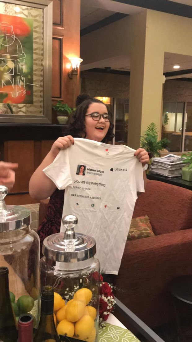 "June Osborn, 14, opens a shirt gifted to her from her date, social media star Michael Gilgan, 16, screen-printed with one of his tweets that reads ""You are my everything."" (Photo by Ireland Gilgan)"