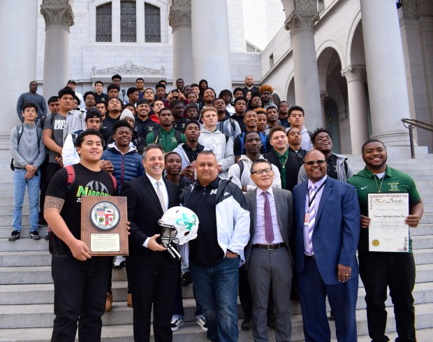 Football players, coaches and school administrators from Narbonne High School gathered on the steps of L.A. City Hall to celebrate their honors from the City Council marking the team's second state championship in three years. The team presented Councilman Joe Buscaino with a helmet signed by the players. Photo by Mayra Ramirez Arriaga
