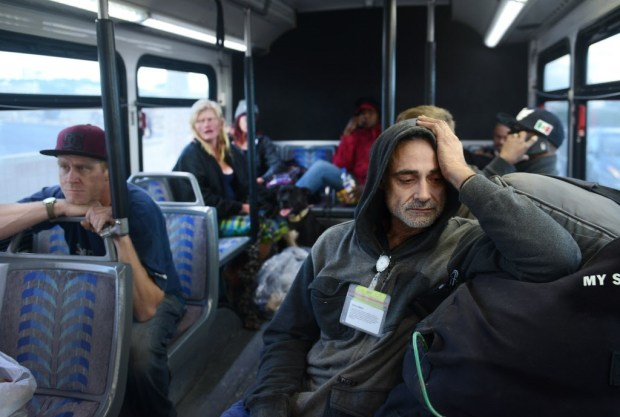 Sean Knutsen ponders his situation as he gets on a bus which will transport him to a hotel in Anaheim. Dozens of homeless people were given rooms at hotels around Orange County (Bill Alkofer, contributing photographer)