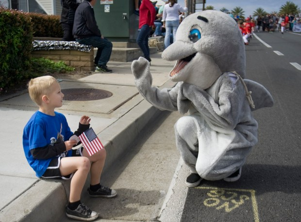 Five-year-old Cole Cooper gets a high-five from the Ocean Institute mascot during the Festival of the Whales Parade in 2016. (Photo by MINDY SCHAUER, ORANGE COUNTY REGISTER/SCNG)