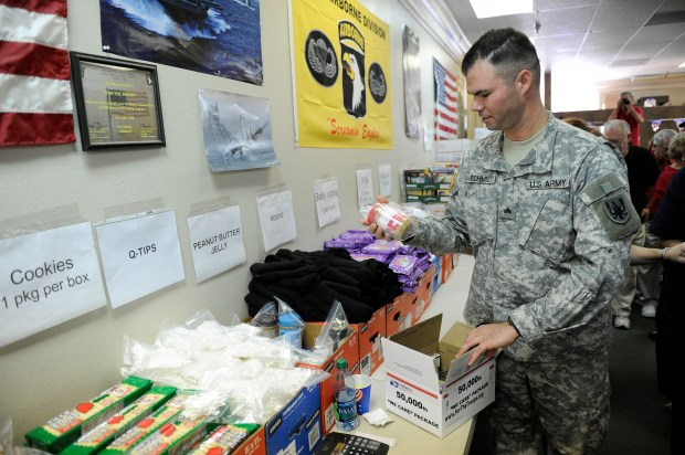 Sgt. Phillip Schmidt packs the 50,000 For The Troops care package at the Simi Valley organization's headquarters Saturday, January 28, 2012. Schmidt was the recipient of the first care package sent by For The Troops and was on hand to hand pack the 50,000 package to be sent overseas. For the Troops sends care packages to front line troops in Afghanistan and Iraq that contain such things as snack items, DVDs, CDs, batteries, personal care items and magazines. (Hans Gutknecht/Staff Photographer)