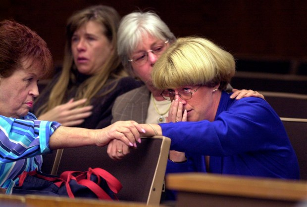 Shaun Rickerl, right, is comforted by neighborhood friends from left, Jo Hilliard, Nikki Hilliard and Carole Suddaby after the guilty verdict was read, convicting her father William Terry Bradford of murdering her mother in 1988. In Torrance Superior Court. Photo by Brad Graverson 4-10-02