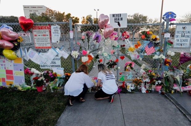 People light candles at a makeshift memorial outside Marjory Stoneman Douglas High School, where 17 students and faculty were killed in Wednesday's mass shooting in Parkland, Fla., Sunday, Feb. 18, 2018. Nikolas Cruz, a former student, was charged with 17 counts of premeditated murder on Thursday. (AP Photo/Gerald Herbert)