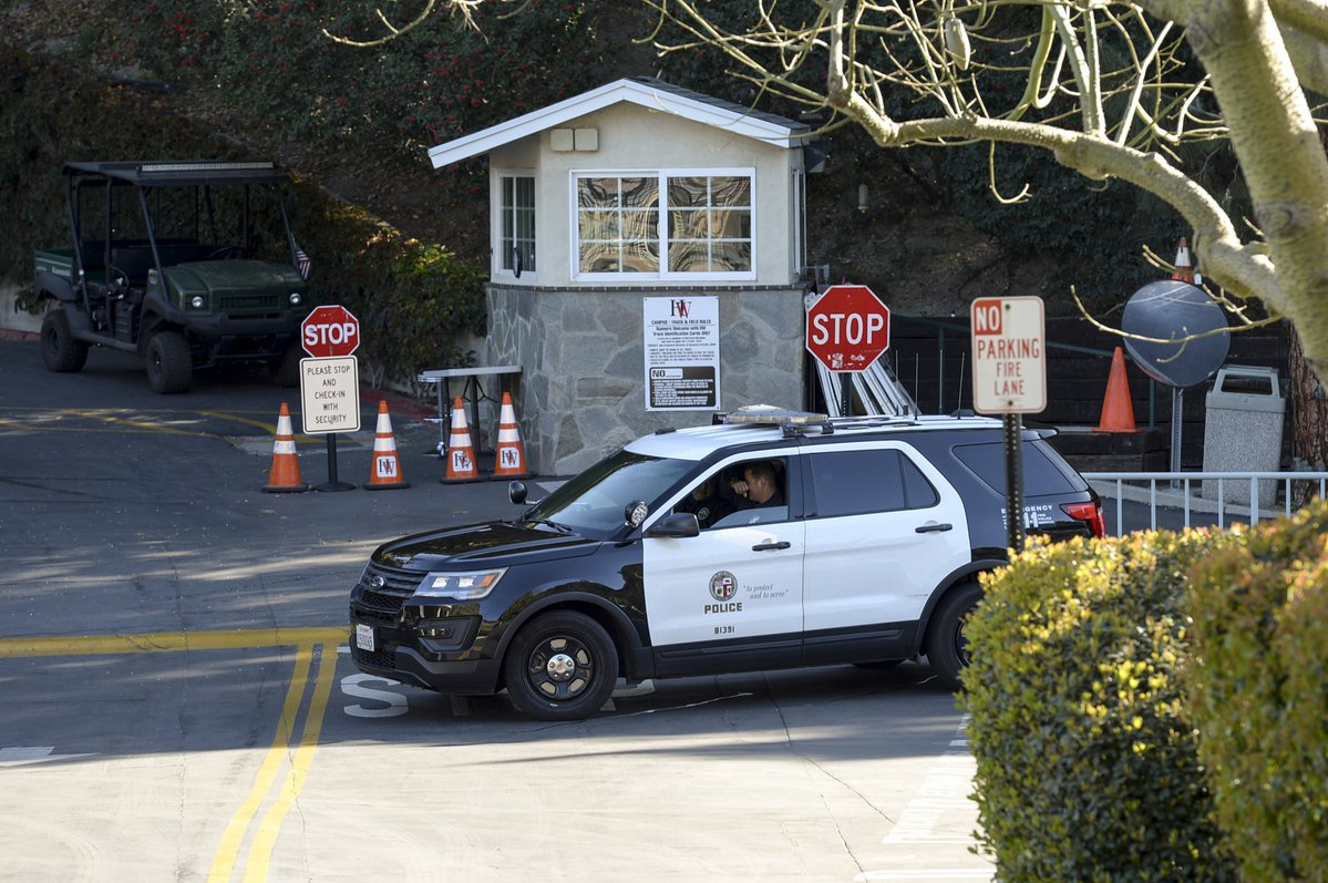 A Los Angeles Police Department officer sits in a patrol vehicle near the entrance of Harvard-Westlake's high school campus in Studio City on Friday Feb. 23 2018. An Instagram post of a gun that mentioned the school led to the campus being closed as a