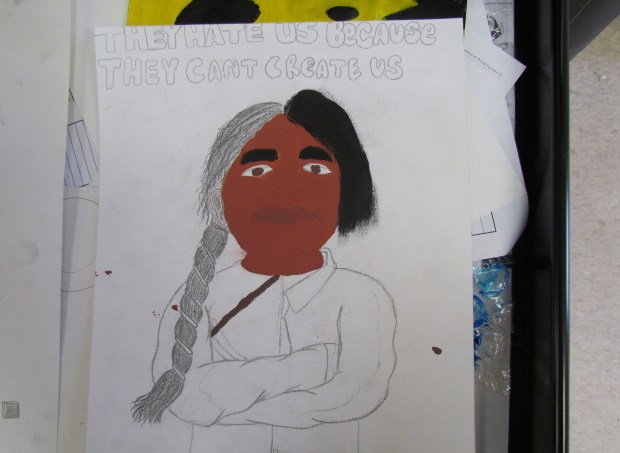A propaganda poster in the works by Noli Indian School Art 2 student Thomas Salgado represents how European settlers tried to transform Native Americans into their own images. (Photo by Diane A. Rhodes, contributing photographer)