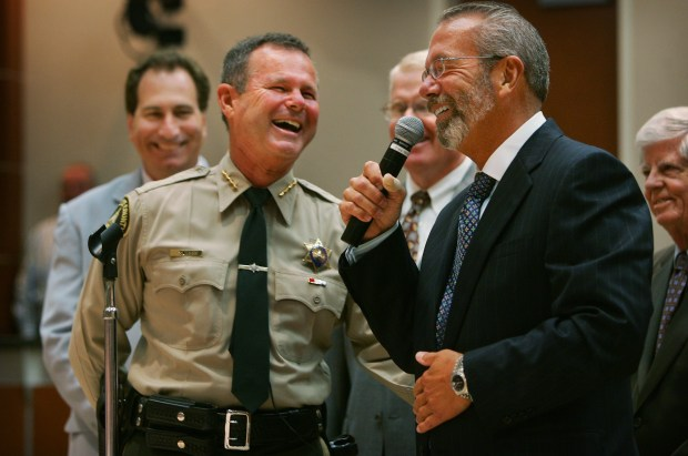 Just before being sworn in as sheriff in October 2007, Stan Sniff, left foreground, shares a laugh with Riverside County supervisors including John Tavaglione, right foreground, and Jeff Stone, background left, both of whom are now criticizing him for his leadership amid budget cuts. (File photo by Kurt Miller, The Press-Enterprise)