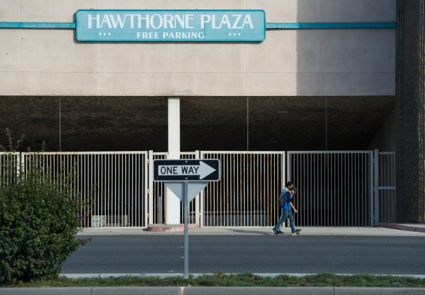Two boys walk past the Hawthorne Plaza parking garage as the mall has been largely vacant since the 1990s and, despite the owner's promises to develop it, progress has completely stalled in Hawthorne Monday, February 12, 2018. (Photo by Thomas R. Cordova / Daily Breeze)