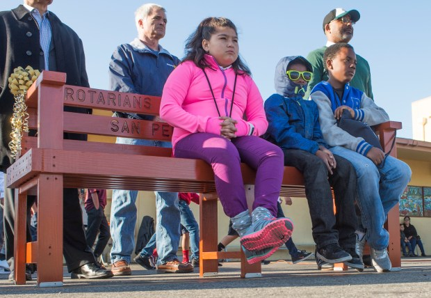 Destiny Garcia, left Elishiel Atlas, Center and Trayvon Franklin, right, sit on the Buddy Bench during a school rally after the Rotary Clubs of Southern California District 5280 delivered the Peace/Buddy Bench at Barton Hill Elementary School in San Pedro Monday, February 26, 2018. (Photo by Thomas R. Cordova / Daily Breeze)