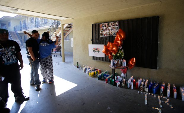 People gather around a memorial for a 16-year old boy fatally shot at an apartment complex courtyard during a police chase in South Los Angeles, Monday, Feb. 5, 2018. Los Angeles County sheriff's officials say deputies fatally shot the boy they believed to be armed during a foot chase on Sunday night. KABC-TV reports Monday that investigators did not immediately recover a suspect weapon. (AP Photo/Damian Dovarganes)
