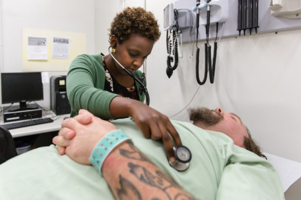 Lello Tesema, a primary care physician and director of population health for the Los Angeles County jails, checks on inmate Michael Callahan on January 17, 2018. Callahan, a 43-year-old carpenter, had uncontrolled diabetes and hypertension when he arrived at the jail. (Heidi de Marco/KHN)
