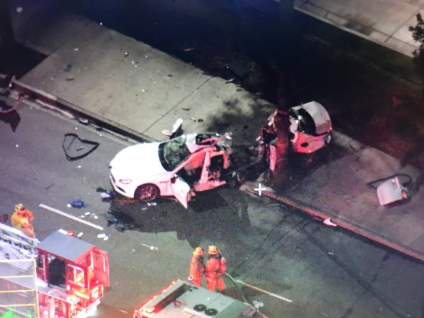 A Maserati that split in half when it struck a tree Friday, March 16, 2018, on Los Coyotes Diagonal near Outer Traffic Circle in Long Beach is seen in an image from the CBS2/KCAL9 helicopter. A man from Idaho died at the scene. (Photo courtesy of CBS2)